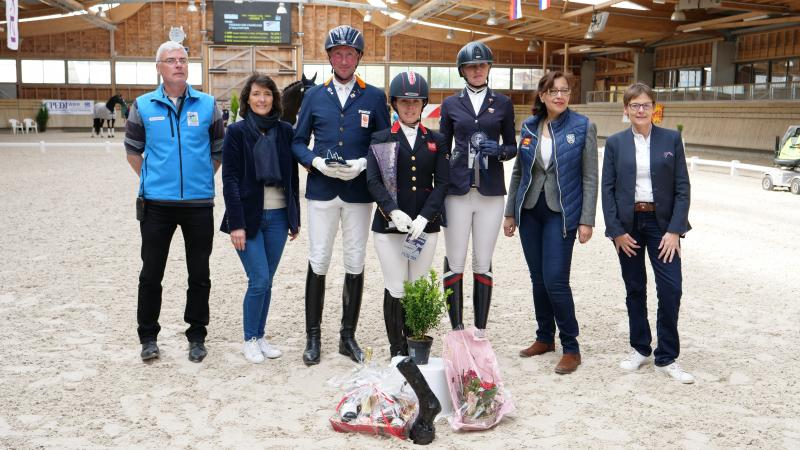 A group of people standing on a dressage arena