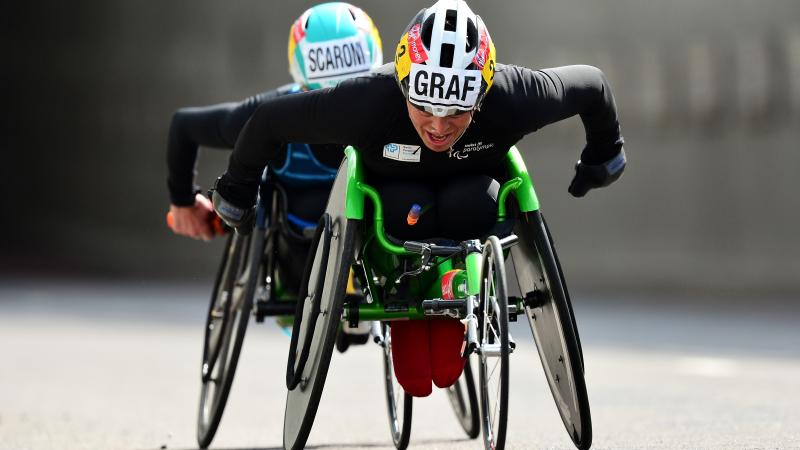 female wheelchair racer Sandra Graf leading another athlete duringa road race