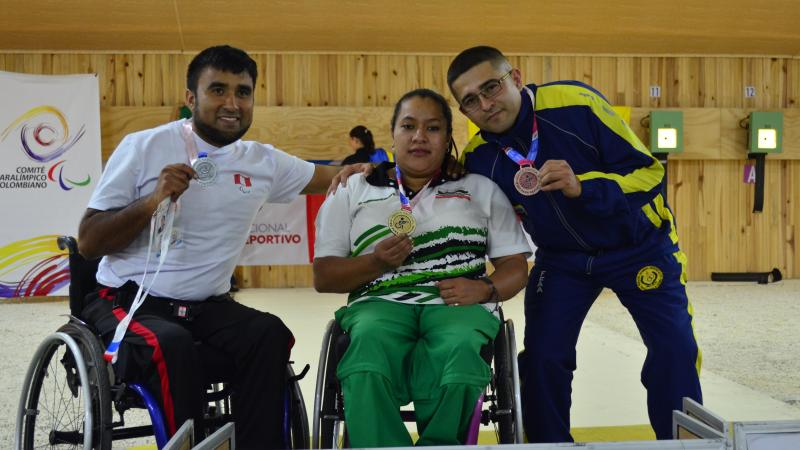 female Para shooter Maria Teresa Restrepo sitting a wheelchair with a male athlete either side holding up medals