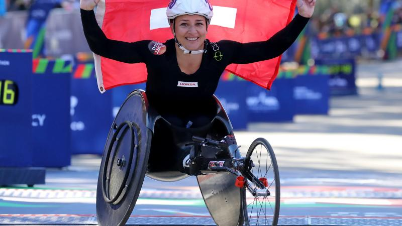 female wheelchair racer Manuela Schaer holding up a Swiss flag