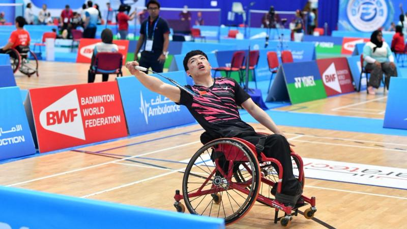 male Para badminton player Qu Zimao goes for a backhand shot on court