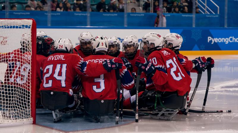 Norwegian Para ice hockey players huddle on an ice rink