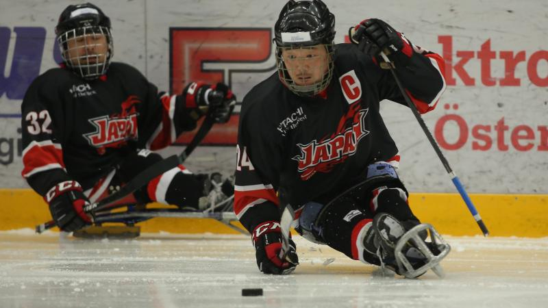 Japanese male Para ice hockey player skates with the puck