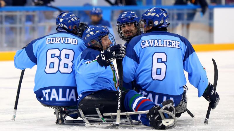 male Para ice hockey player Nils Larchi being hugged on the ice by his teammates
