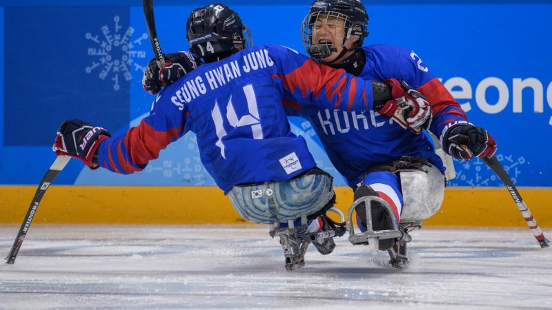 Two Para ice hockey players hug on the ice rink