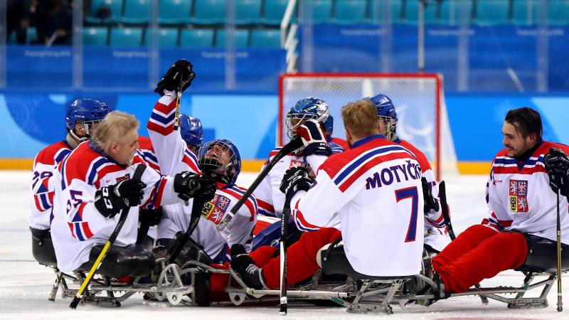 male Para ice hockey players from Czech Republic celebrating and hugging on the ice