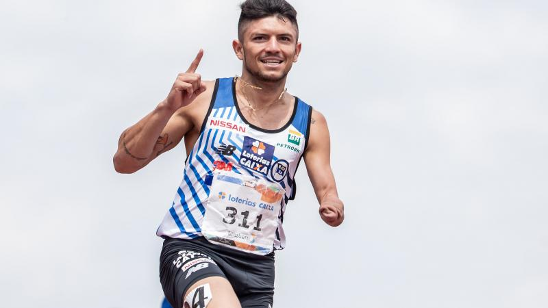 male Para athlete Petrucio Ferreira raises his finger as he crosses the finish line