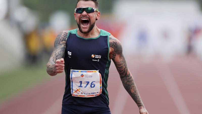 male Para athlete Vincent Rodrigues yells out as he crosses the finish line to win the race