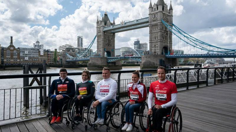 Five wheelchair athletes sitting in a row at the edge of the River Thames with London's Tower Bridge in the background