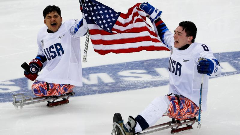 two male US Para ice hockey players on the ice holding a USA flag