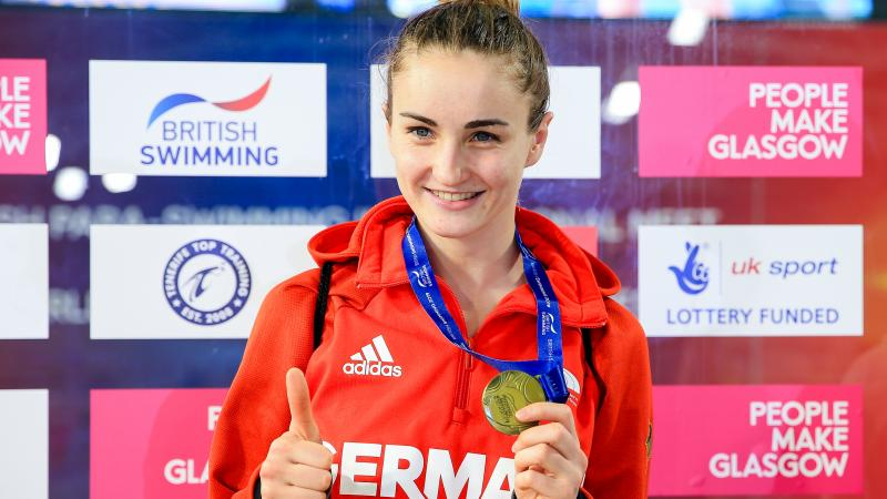 female Para swimmer Elena Krawzow gives a thumbs up and holds up her gold medal