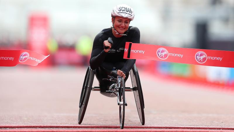 Female wheelchair racer Manuela Schaer breaks the tape at the finish line