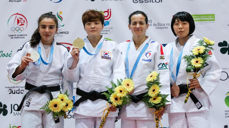 female judoka Sandrine Martinet on the podium holding her medal