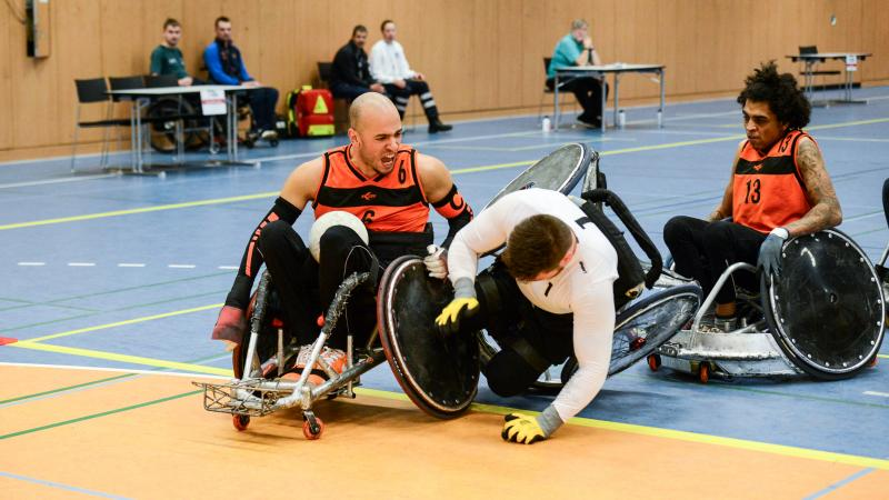 Two men in wheelchair chairs collide playing wheelchair rugby