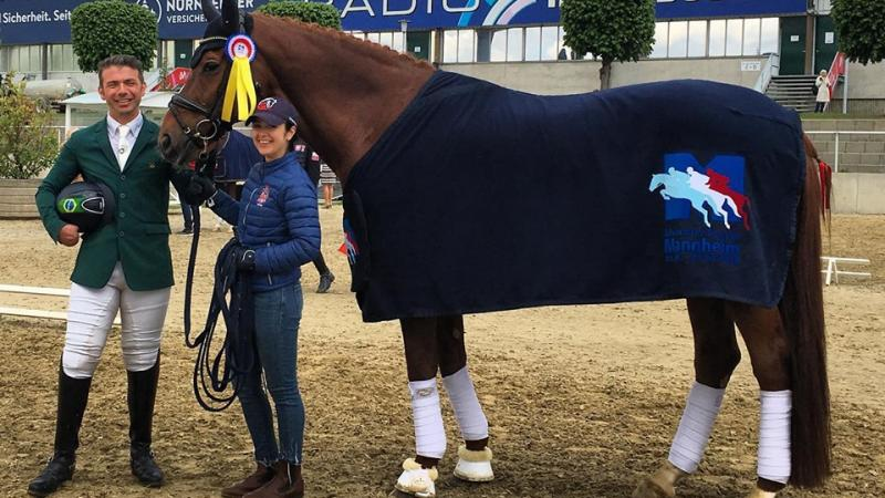 Brazilian Para dressage rider posing with his horse and a staff member for a photo