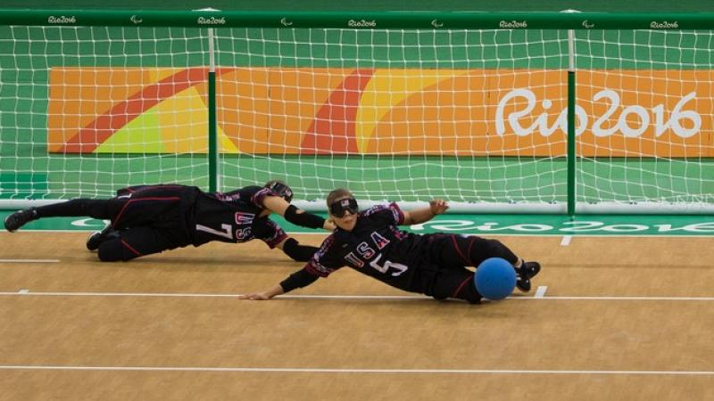 female goalball players Eliana Mason and  Amanda Dennis dive to stop the ball
