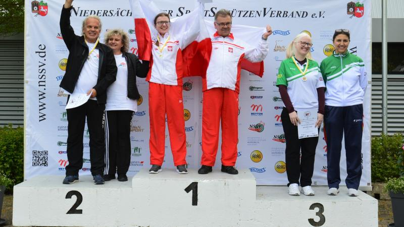 Three vision impaired shooting Para sport athletes on the podium with their guides
