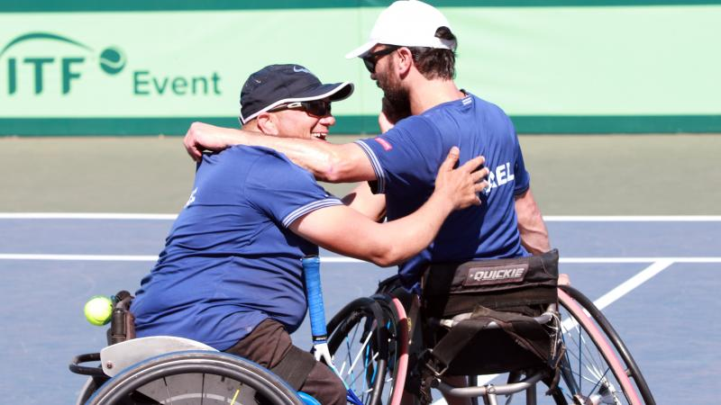 two male wheelchair tennis players from Israel hug on a hard court