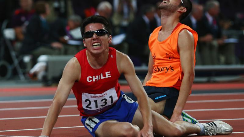 Chilean athlete and his guide on the floor exhausted after a race