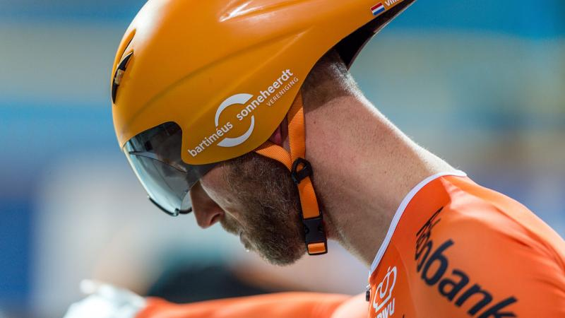 Dutch cyclist Vincent Ter Schure looking down while wearing a competition helmet and orange gear
