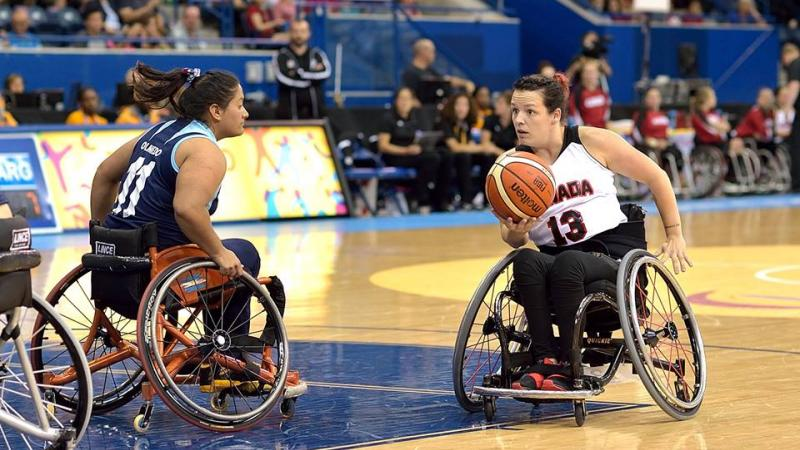 Canadian wheelchair basketball player holds the ball as an Argentinian defender tries to prevent her from scoring