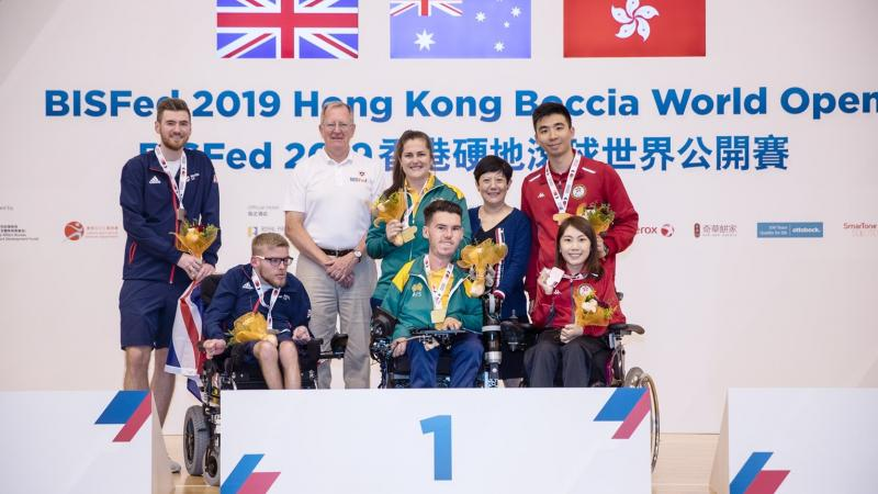 Podium photo with three boccia players and their assistants posing for a photo