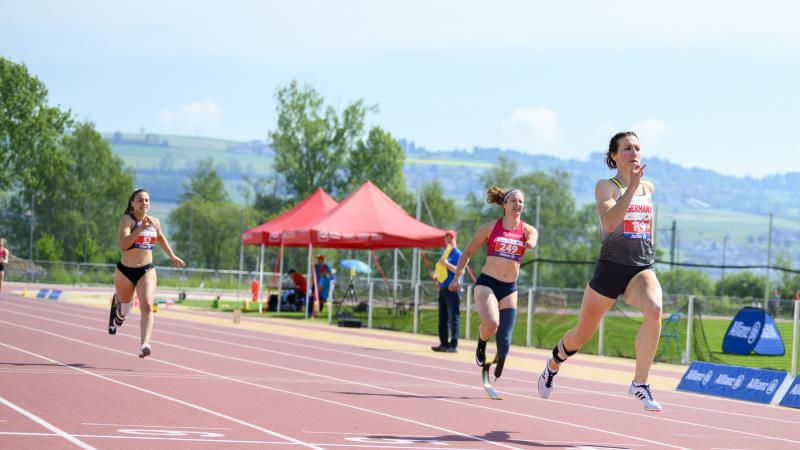 German female sprinter leads ahead of three other runners