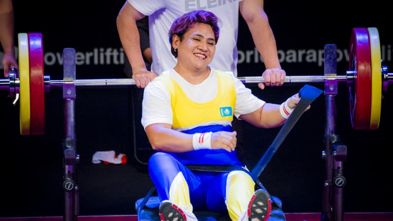 Raushan Koishibayeva smiling while sitting on the bench after her lift