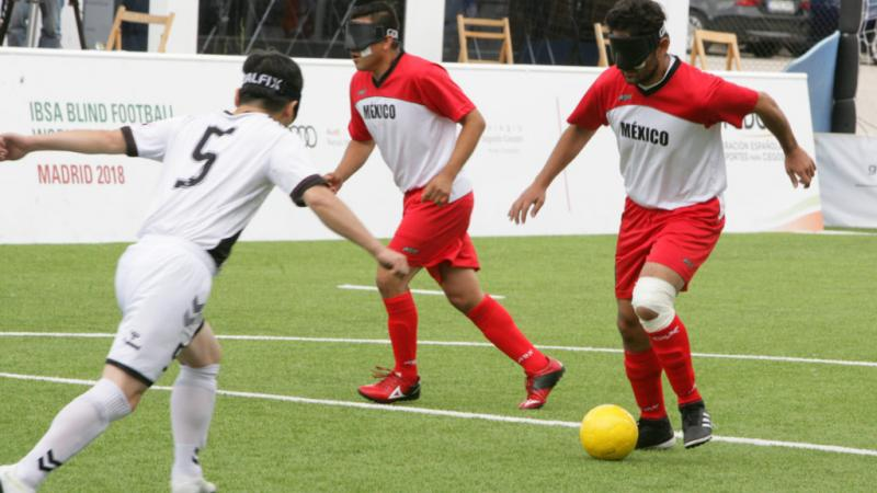 Mexican blind football player Jorge Lanzagorta controls the ball and faces South Korean defender