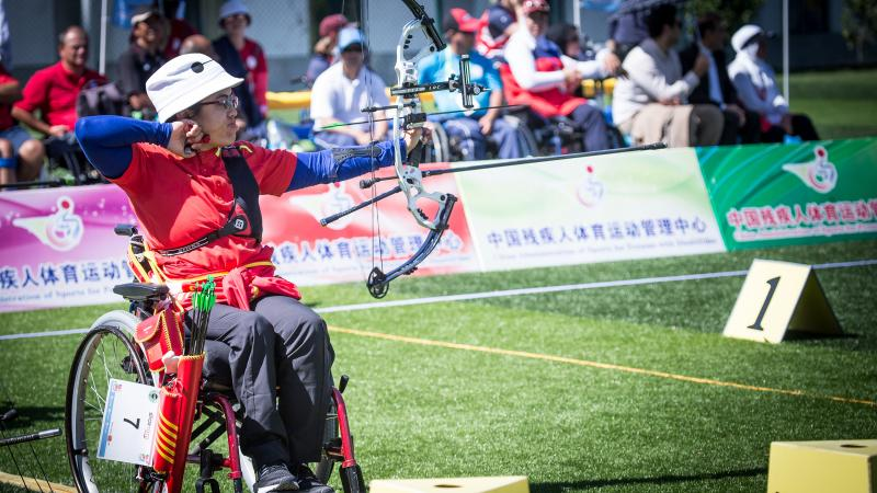 Chiense female archer in a wheelchair pulls back on her bow string