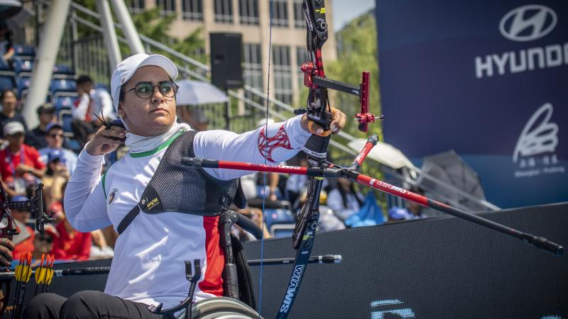 Female Iranian archer in a wheelchair looks on as she releases her arrow