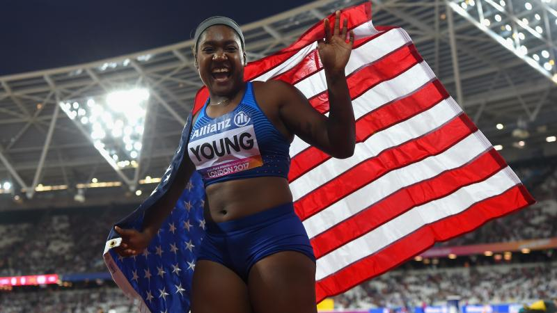 Deja Young laughs while waiving the US flag