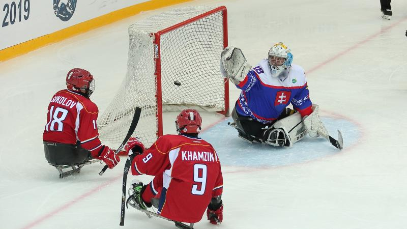 Two Russian Para ice hockey players in front the Slovakian goaltender
