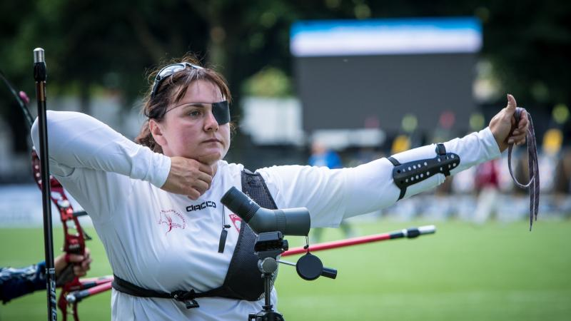 Polish woman with eye patch looks on after shooting her arrow