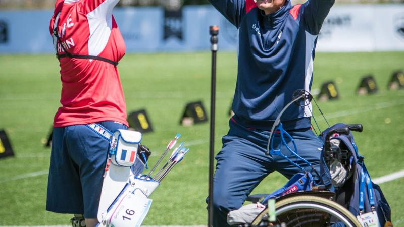 female Para archer Julie Chupin raises her arms in celebration with her coach