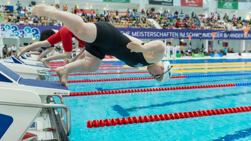 A short stature female swimmer jumping in the water in front of other swimmers