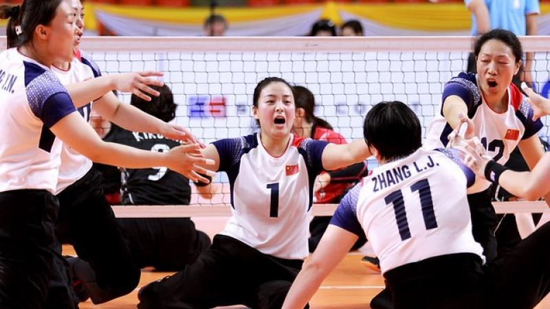 Chinese female sitting volleyball players celebrate a point