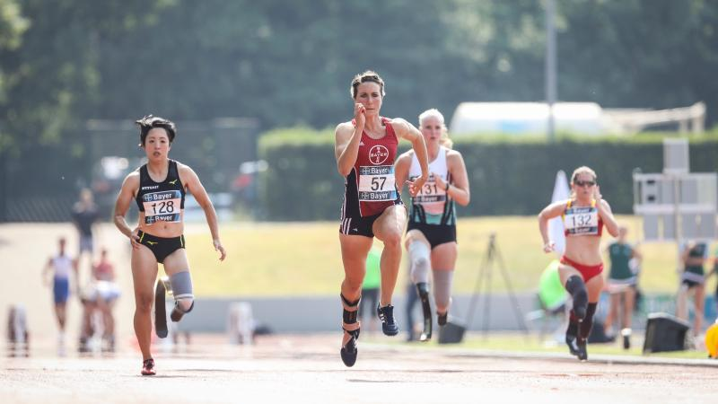 Four female Para athletes running in a track
