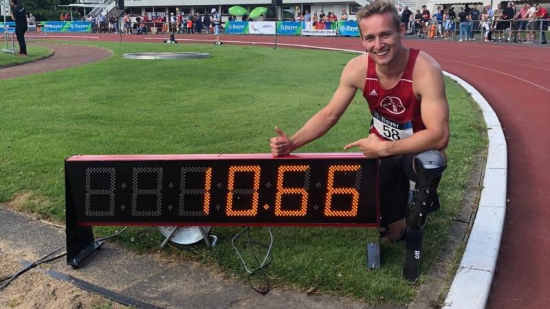 German male sprinter poses next to a clock that says 10.66