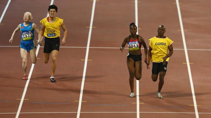 Two female vision impaired sprinters racing with their guides