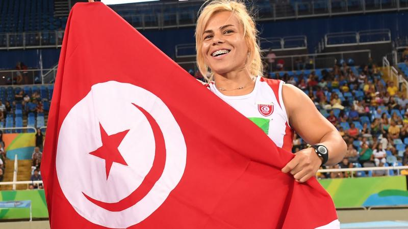 female Para athlete Raoua Tlili holds up the Turkish flag and smiles