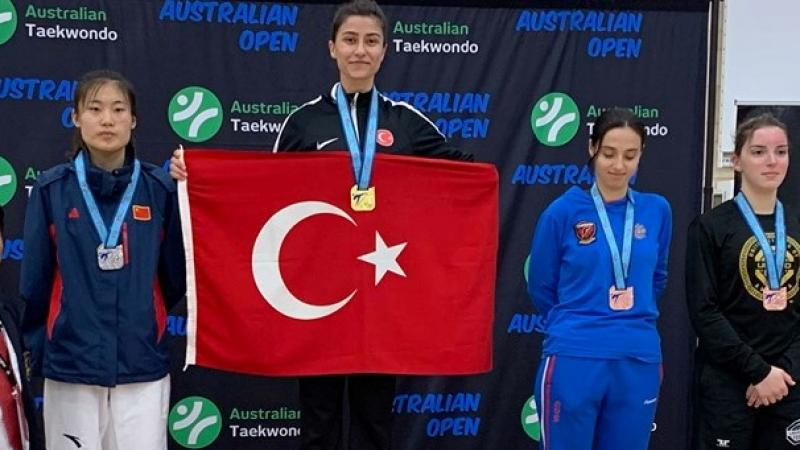 Woman taekwondo fighter on the podium holding the Turkey flag