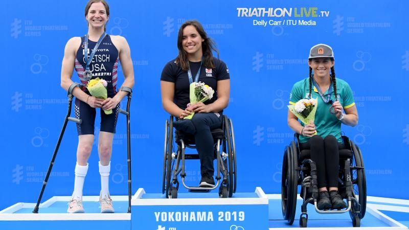 Three female triathletes on a podium smiling