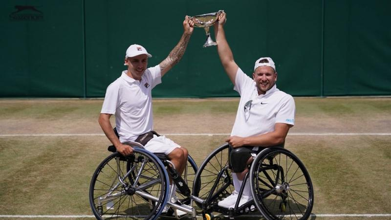 Two male wheelchair tennis players holding a trophy on a grass court