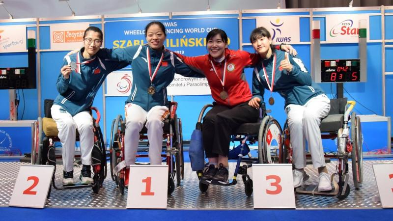 Four female wheelchair fencers put arms around each other and pose on a podium