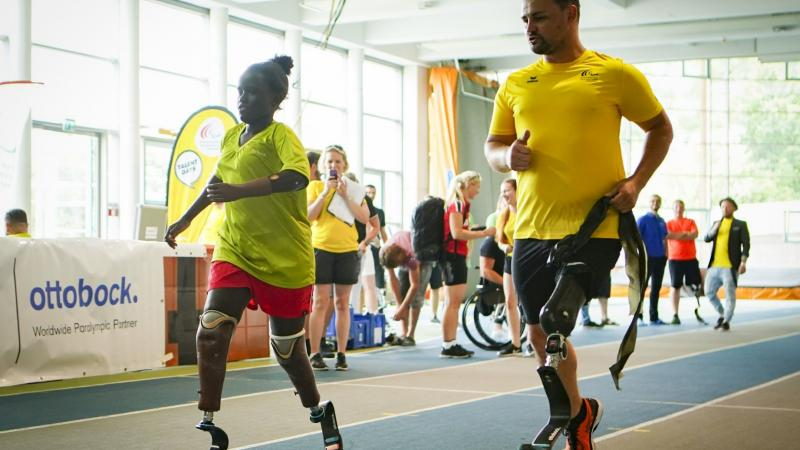 Male sprinter with prothesis runs alongside a young double-amputee sprinter girl