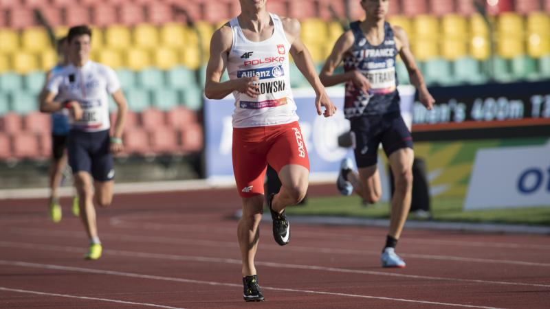 A male sprinter runner ahead of two other competitors