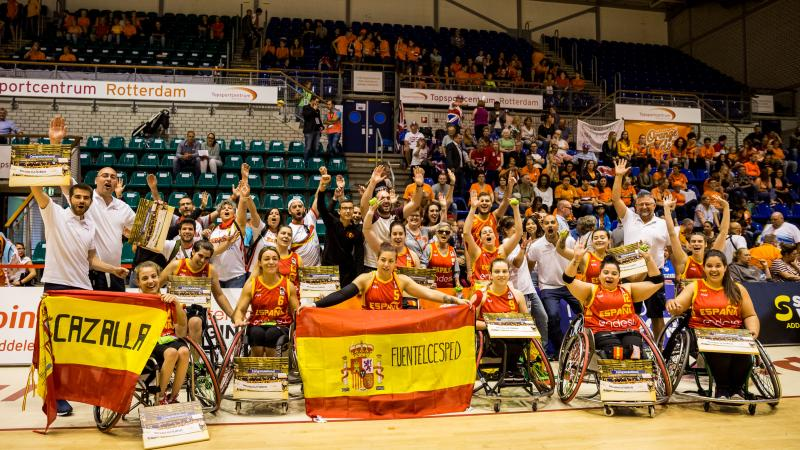 Spanish women's wheelchair basketball team and their staff celebrate as a group holding their hands up