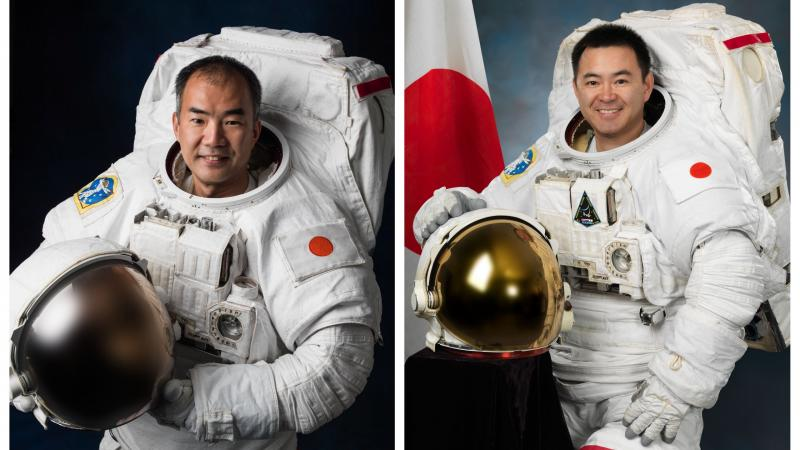 two male astronauts smiling in their space suits and standing beside the Japan flag