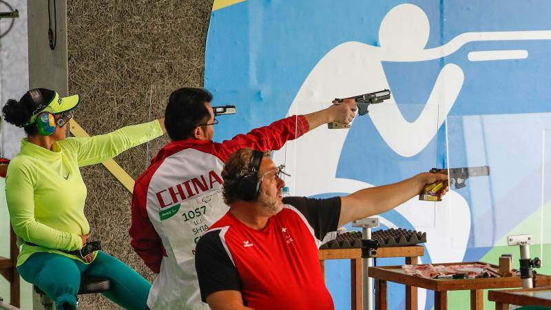A one-legged woman and two men competing at a shooting range
